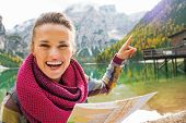 stock photo of south tyrol  - Young woman with map on lake braies in south tyrol italy pointing - JPG