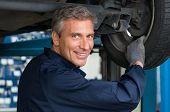 picture of maturity  - Portrait Of Happy Mature Mechanic At Repair Service Station Changing Tire - JPG