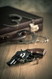 image of revolver  - Vintage revolver and bullet with briefcase and handcuffs on background. ** Note: Shallow depth of field - JPG