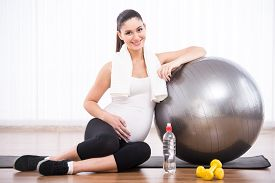 picture of pregnancy exercises  - Pregnant woman is doing exercises with gymnastic ball - JPG