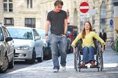 stock photo of rollator  - boy is walking next to a girl on a wheelchair - JPG