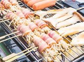 stock photo of grilled sausage  - Grilled bacon and mushroom rolled with sausages on electrical grilled - JPG