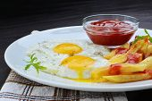 image of french fries  - Fried eggs with french fries and ketchup on white plate over wooden table - JPG