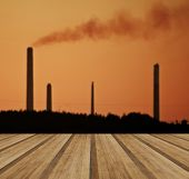 stock photo of chimney  - Industrial chimney stacks polluting the air in a natural landscape setting with wooden planks floor - JPG