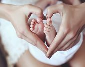foto of baby feet  - tender interior photo of cute baby feets in mom hands holding them in heart shape - JPG
