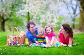 foto of little young child children girl toddler  - Young family with kids having picnic outdoors. Parents with two children relax in a blooming summer garden. Mother father little girl and baby boy eat sandwich and fruit drink juice for healthy lunch in a park. ** Note: Shallow depth of field - JPG