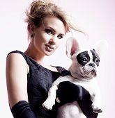 stock photo of pug  - Elegant beautiful blonde woman posing witg pug dog over pink background - JPG