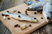 foto of cod  - Salty stockfish cod on wooden board with gaarlic and pepper - JPG