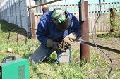 image of erection  - welder outdoor working and soldering iron with mask - JPG
