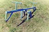 picture of seesaw  - Old blue seesaw in the park playground for kids - JPG