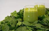 stock photo of roughage  - Green smoothies in wine glasses surrounded by spinach leaves - JPG