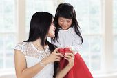 stock photo of give thanks  - Cute little girl giving present to her mother at home symbolizing thankful to parent - JPG