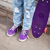 foto of snickers  - Teenager in blue jeans and gumshoes stands with skateboard near gray urban wall - JPG