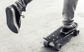 stock photo of snickers  - Feet of a skateboarder in jeans and gumshoes monochrome retro stylized photo - JPG