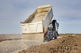 picture of dumper  - Tipping truck unloading gravel on road construction site - JPG