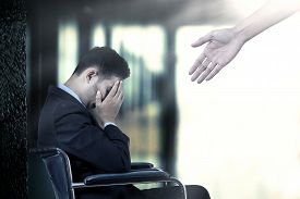 stock photo of wheelchair  - Frustrated businessman sitting on a wheelchair get a help from a hand - JPG