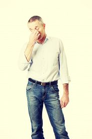 stock photo of sinuses  - Mature man holding his nose because of sinus pain - JPG
