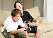 Two boys playing video games with intense competition.