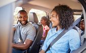 Young black family in a car on a road trip smiling poster