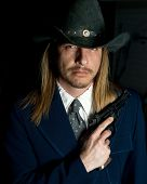 stock photo of gunslinger  - A long haired man in cowboy hat holds a revolver - JPG