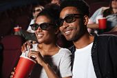 Smiling attractive afro american couple watching 3D movie and eating popcorn while sitting in a movi poster