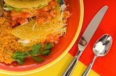 picture of mexican food  - Mexican food plaate with tacos bean and rice on brightly colored plate with flatware - JPG
