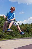 Постер, плакат: Молодой мальчик будет воздухе с его скутер