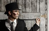 stock photo of illuminati  - Fantastical stylized portrait of man in top hat and and cane in surrealistic makeup - JPG