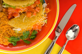 foto of mexican food  - Mexican food plaate with tacos bean and rice on brightly colored plate with flatware - JPG