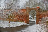 Brick wall with path through arch in snowy park