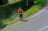 City Maintenance Worker Cutting Weed On The Road Shoulder With A Strimmer poster