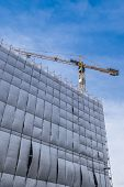 Building Facade Renovation With Cellophane As Protection And Crane, Against A Blue Sky With White Cl poster