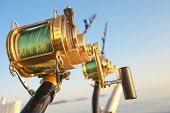 stock photo of game-fish  - big game fishin reels and rods lit by setting sun - JPG