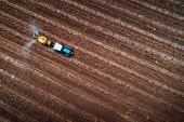 Aerial View Of Tractor Spraying Vineyard With Fungicide poster