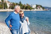 Senior Couple Is Hugging And Walking At Sea Beach Outdoor. Happy Man And Woman Are Relaxing, Traveli poster