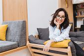 Portrait Young Brunette Woman In Black Glasses Chilling On Couch In Modern Apartment. Comfortable, C poster