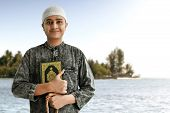 Religious Muslim Man Holding Quran And Rosary Beads poster