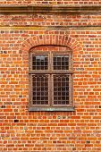 Brick Wall Of Old Castle With Window. Glass Panel Window In A Brick Wall. A Window In An Old Brick B poster