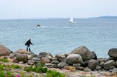 Woman Fishing On Rocky Shore. Woman Fisher On A Stone Boulder Throws A Fishing Rod Into Sea. Woman W poster