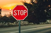 A Traffic Sign Stop In Coastline With Road  And Sea On Background - Photo On Sunset. Illuminated Sig poster
