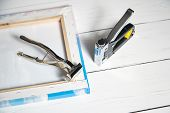 Canvas Pliers And Stapler On White Wooden Table. Tools For Wrapping  Canvas On Stretcher Bar poster