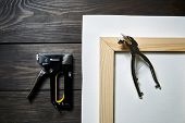 Stretching Canvas On Wooden Stretcher Bar, Staple Gun And Canvas Pliers On A Brown Table poster