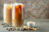 Ice Coffee In A Tall Glass With Cream Poured Over And Coffee Beans. Cold Summer Drink On A Brown Rus poster