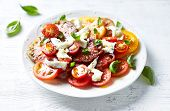Mixed tomato salad with mozzarella cheese and basil leaves. Mediterranean cuisine poster