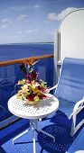foto of cruise ship  - balcony on a cruise ship with chair and flowers on table on ocean water - JPG