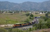 stock photo of boxcar  - A mountain freight train climbs slowly up to Tehachapi - JPG