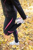 stock photo of leggins  - Woman in black leggins standing on one foot for stretching leg - JPG