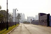 stock photo of hazy  - An empty street with lamp posts and factories and a hazy durban south africa skyline in the background - JPG