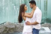 stock photo of flirt  - Young sensual couple in city center near fountain - JPG