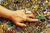 stock photo of thrift store  - A woman explores a huge pile of vintage rings - JPG
